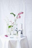 Forget-me-nots, lily of the valley, foamflowers and bleeding heart in bottles on table with white tablecloth