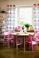 Pink wooden chairs around round table below window with floor-length, floral curtains