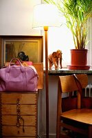 Standard lamp with white lampshade, pink handbag on chest of drawers and wooden chair