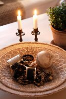 Beaded jewellery and old baseball in flat basket next to lit candles in vintage candlesticks