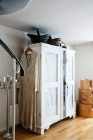 Long dress on coat hanger hung on white-painted wardrobe with dark baskets on top