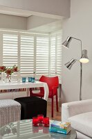 View across coffee table to white dining table, red chair and retro standard lamp in modern interior with white louver blinds