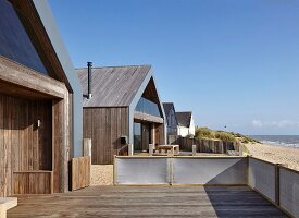 Camber Sands Beach Houses, Rye, United Kingdom. Architect: Walker and Martin, 2014; View along beach showing neighbouring beach houses.