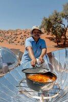 Elisabeth Lammert im NaDEET (Namib Desert Environmental Education Trust) at a solar cooker, NamibRand Nature Reserve, Namibia, Africa