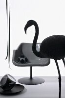 Still-life arrangement with silhouette of flamingo and camera on shell chair
