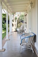 White rattan chair against wall of cottage veranda with white wooden structure