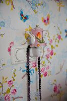 Night light shaped like vintage teapot against wallpaper with pattern of butterflies