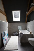 Pale rug on grey-tiled floor in modern, attic bathroom with half-height tiled walls