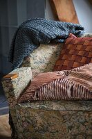 Armchair with vintage cover and patterned scatter cushions
