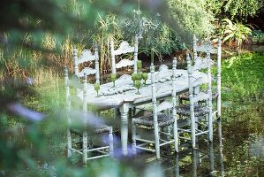 Set table and rush-bottom chairs standing in pond