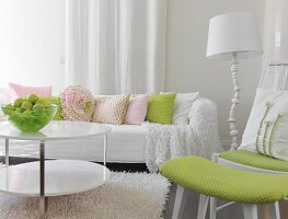 White couch with pastel scatter cushions, fruit bowl on coffee table and chair with matching foot stool