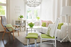 Romantic living room - chair with green seat cushion and matching footstool, armchair and comfortable white sofa around coffee table