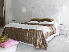 Double bed with white upholstered headboard and green blanket in bedroom with pendant lamps and motto in white on wall