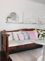Antique bench with scatter cushion and white seat cushion below candlesticks on shelf on wall