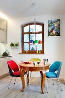 Brightly coloured, retro, upholstered chairs around antique, exotic-wood table below colourful, spherical pendant lamps in open-plan kitchen