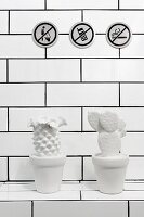 Three prohibitory pictograms on tiled wall and white cactus ornaments on masonry shelf