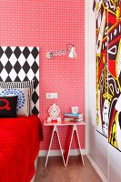 Eclectic bedroom with red, patterned wallpaper, black and white bed headboard, whimsical bedside table and modern artwork