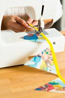 Making bunting from colourful triangles of fabric using a sewing machine