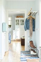 Wood-clad hallway in pastel shades with coat rack and view of dresser though open door in rustic interior