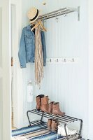 Open-plan cloakroom with shelf, denim jacket and straw hat on hooks, shoes on metal shoe rack and wood-clad walls