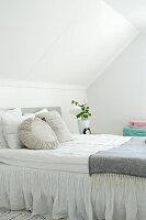 Stacks of scatter cushions in various shades of white and grey on box-spring bed in attic bedroom