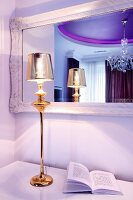 Gold-coloured, elegant table lamp in front of hand-crafted mirror in glamorous bedroom