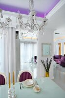Elegantly set dining table and crystal chandeliers in open-plan, white, designer interior