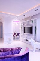 Open-plan, elegant, white living area with purple accents, indirect lighting and plasma TV on open-fronted shelves