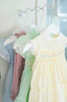 Pastel, ruched dresses on clothes hangers hung from bracket