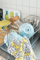 Blue bowls and patterned tea towel on draining rack next to sink