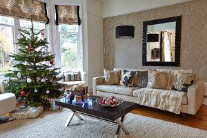 Decorated Christmas tree, coffee table with dark top, sofa and arc lamp in living room