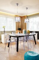 Plastic chairs around dark table below pendant lamps with transparent lampshades in dining room