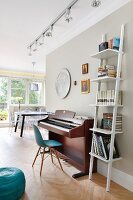 White ladder shelves next to piano and classic chair against grey-painted wall; lighting strip with spotlights and dining area in background