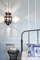 Moroccan-style pendant lamp casting pattern of light on wall next to metal lattice headboard of metal bed