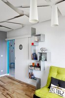 Zig-zag shelves between sliding door with porthole and green futon sofa