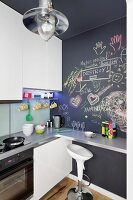 Designer bar stool at counter on chalkboard wall in fitted kitchen