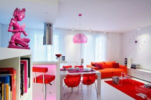 Red shell chairs at dining table in front of orange sofa and red rug