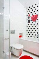 Toilet next to bathtub in white bathroom with polka-dot wall