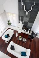 View down onto elegant, white leather sofa set in front of fireplace integrated into wall covered in slate tiles