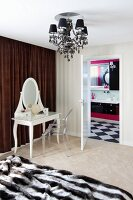 White, postmodern dressing table with vanity mirror and Ghost chair in front of brown curtain next to to open door with view into bathroom