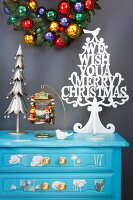 Stylised Christmas tree on pale blue chest of drawers