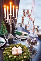 Advent calender and lit candles in candelabra on set table