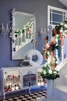 Staircase balustrade decorated with fir branches in front of mirror on grey wall above sideboard