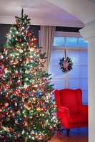 Red armchair next to magnificently decorated Christmas tree in living room