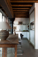Table lamp on rustic wooden table an classic cantilever chairs in open-plan, modern kitchen with traditional metal pillar