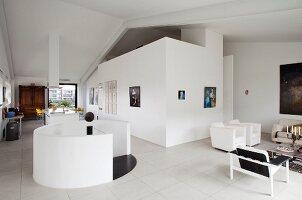 Modern loft apartment with round white balustrade around stairwell and minimalist lounge area