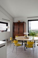 Yellow retro chairs at round table and antique cupboard in corner next to floor-to-ceiling window