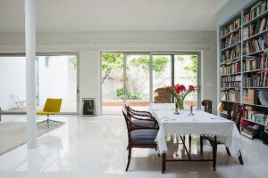 Table with white tablecloth and armchairs opposite bookcase in loft apartment: terrace doors with view into courtyard in background