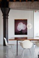 White classic chairs around dining table in front of modern artwork on wall in restored loft apartment