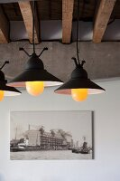 Lit, vintage pendant lamps below exposed, rustic roof beams, concrete girder and photograph on wall in loft apartment
